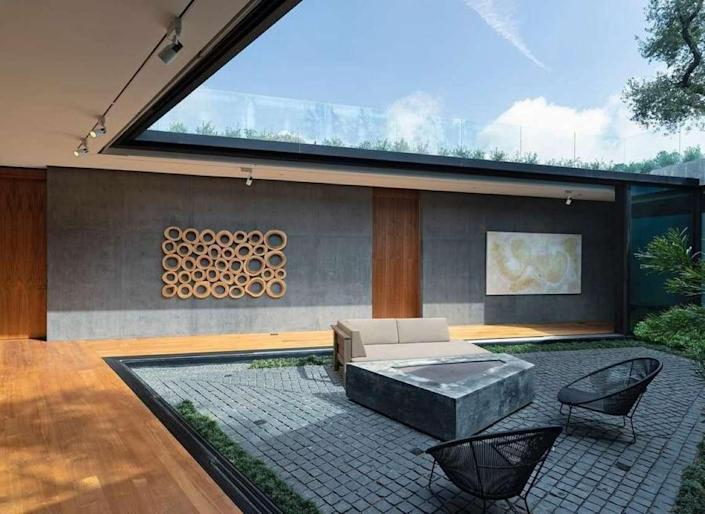 A tranquil, concrete sunken courtyard lays at the heart of Kao's new mansion.