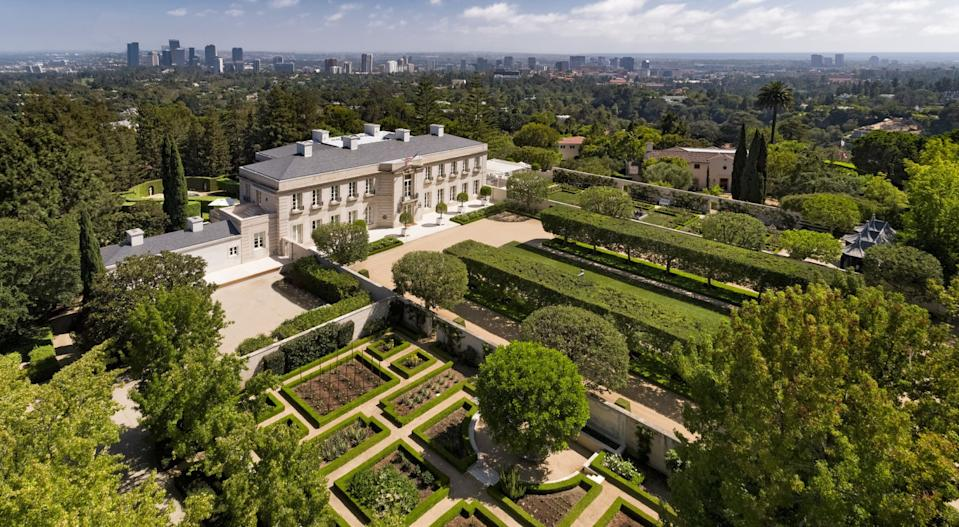 Aerial view of Chartwell mansion with manicured gardens and a city skyline in the background