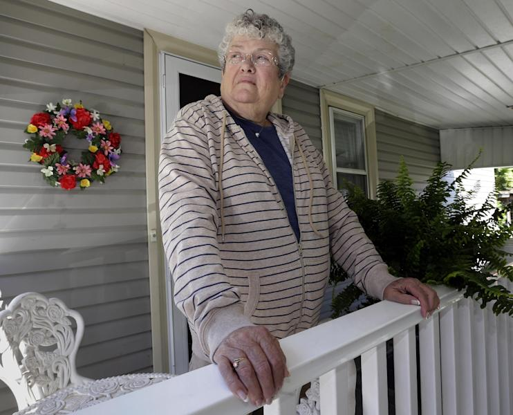 Former school bus monitor Karen Klein stands on the porch at her home in Greece, N.Y., Wednesday, June 19, 2013. She reflected on the year since the taunts and threats she endured from four seventh-grade boys moved thousands of strangers to give her money for a vacation. More than $700,000 poured in. (AP Photo/David Duprey)