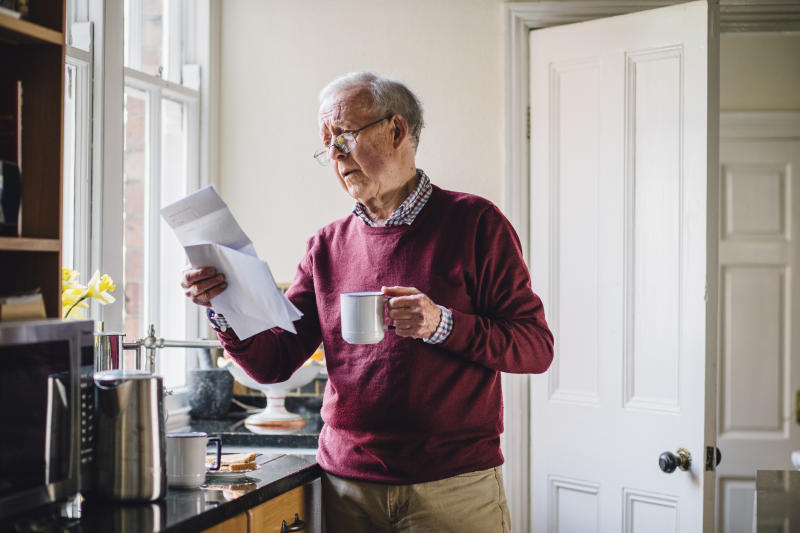 An older man standing in his kitchen holding a mug in one hand and papers in another