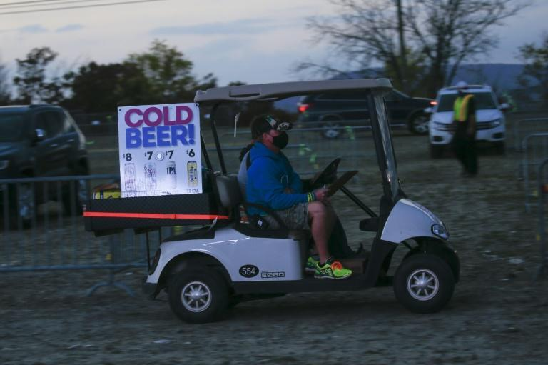 """The """"bar"""" at the Disco Biscuits concert -- a golf cart drives between rows of parked cars delivering drinks that party-goers purchased on an app"""