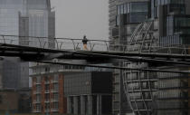 A runner crosses the Millennium Bridge as the coronavirus lockdown continues in London, Thursday, March 25, 2021. All gyms remain closed until at least April. (AP Photo/Kirsty Wigglesworth)