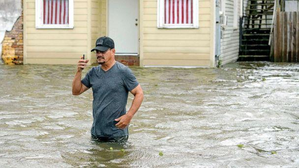 PHOTO: A man talks on his smartphone as he wades through storm surge from Lake Pontchartrain on Lakeshore Drive in Mandeville, La., as Hurricane Barry approaches, July 13, 2019. (Matthew Hinton/AP)