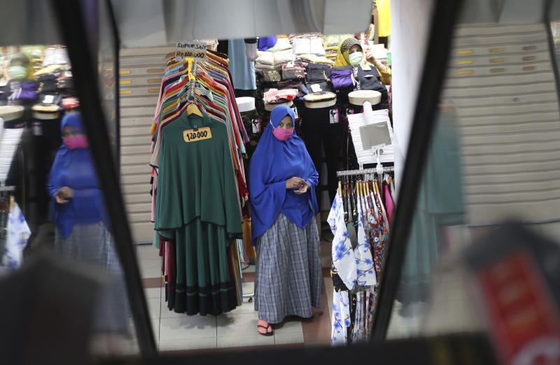 Cloth venders wearing face mask wait customers amid fears of the new coronavirus outbreak at a market in Jakarta, Indonesia Tuesday, June 30, 2020.(AP Photo/Achmad Ibrahim)