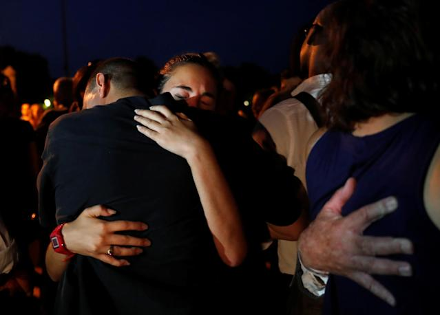 <p>Capital Gazette staffers embrace after a candlelight vigil in downtown Annapolis to honor the five people who were killed inside the Capital Gazette newspaper the day before in Annapolis, Md., June 29, 2018. (Photo: Leah Millis/Reuters) </p>