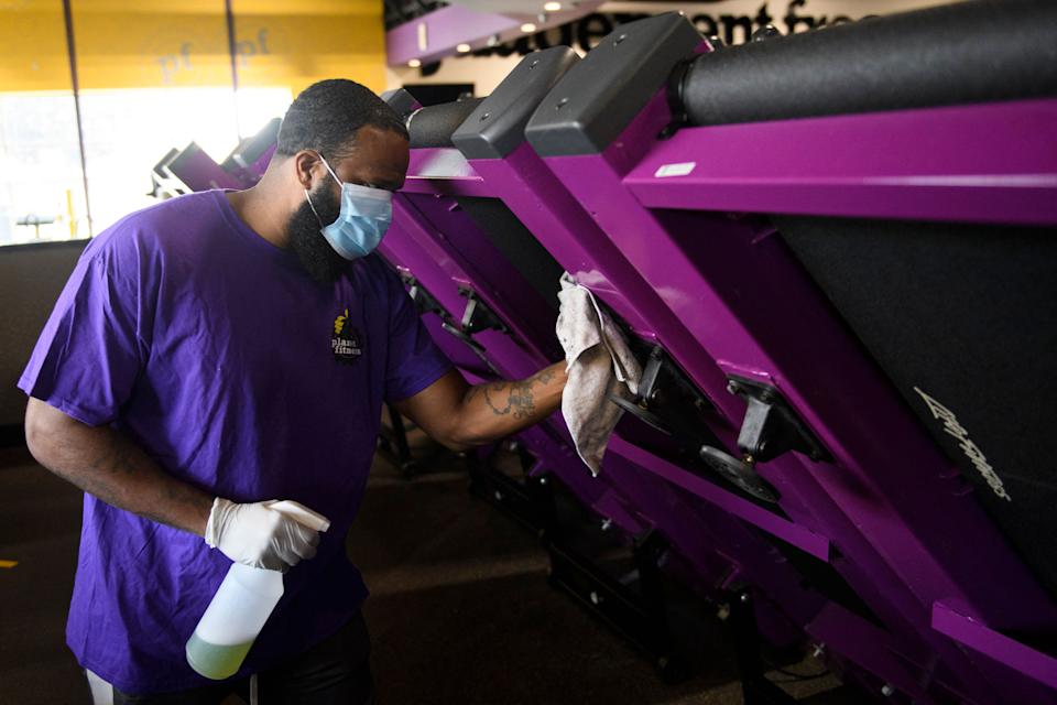 A man carrying a spray bottle and rag cleans fitness equipment.