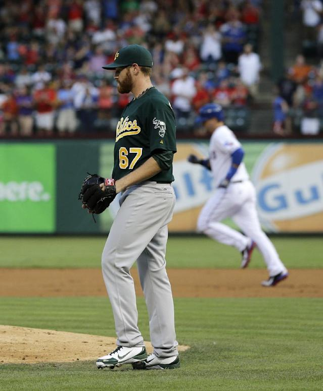 Oakland Athletics starting pitcher Dan Straily (67) walks back to the mound after giving up a two-run home run to Texas Rangers' A.J. Pierzynski, rear, in the second inning of a baseball game, Monday, June 17, 2013, in Arlington, Texas. (AP Photo/Tony Gutierrez)