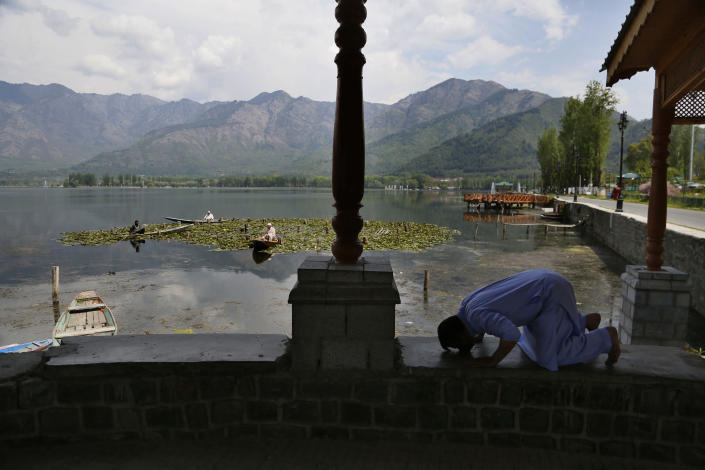 A Kashmiri Muslim man offers prayer on the banks of Dal Lake on the second day of Ramadan during lockdown to prevent the spread of the new coronavirus in Srinagar, Indian controlled Kashmir, Sunday, April 26, 2020. (AP Photo/Mukhtar Khan)