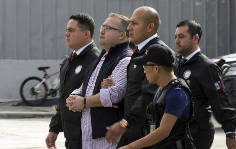 Mexico's ex-governor of Veracruz state, Javier Duarte, is escorted in handcuffs by police to an aircraft as he is extradited to Mexico City, at an Air Force base in Guatemala City, Monday, July 17, 2017. Duarte faces charges of embezzlement and ties to organized crime in his home country. (AP Photo/Moises Castillo)
