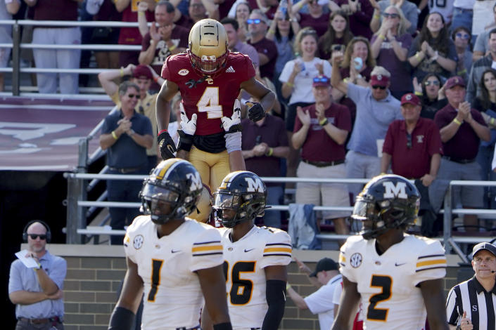 Boston College wide receiver Zay Flowers (4) is lifted by teammates after scoring a touchdown as Missouri players react during the overtime period of an NCAA college football game, Saturday, Sept. 25, 2021, in Boston. (AP Photo/Mary Schwalm)