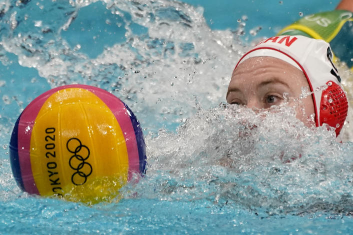 Canada's Hayley McKelvey swims after the ball during a preliminary round women's water polo match against Australia at the 2020 Summer Olympics, Saturday, July 24, 2021, in Tokyo, Japan. (AP Photo/Mark Humphrey)