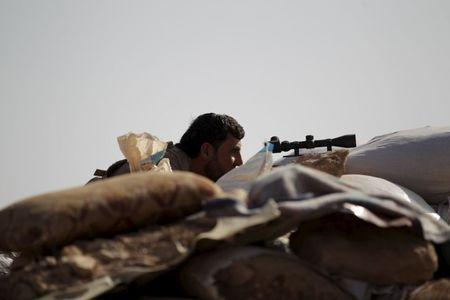 A Free Syrian Army fighter of the 101 Division takes a position behind sandbags near the town of Morek in the northern countryside of Hama, Syria October 14, 2015. REUTERS/Khalil Ashawi