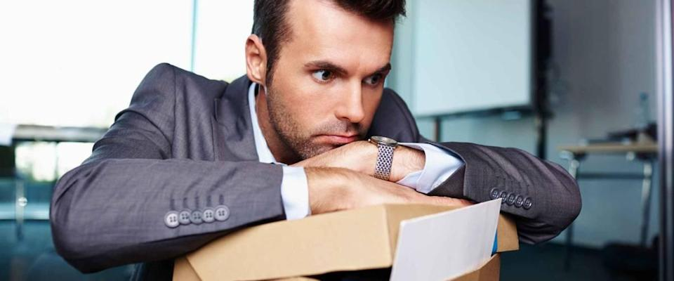 Businessman fired from work sitting sad at office