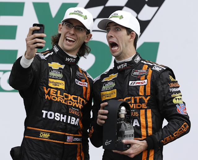 Jordan Taylor, left, and his brother Ricky Taylor take a photo of themselves in Victory Lane after they placed second in the IMSA Series Rolex 24 hour auto race at Daytona International Speedway in Daytona Beach, Fla., Sunday, Jan. 26, 2014.(AP Photo/John Raoux)
