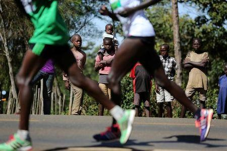 Athletes run on a road during a half marathon near the town of Eldoret in western Kenya