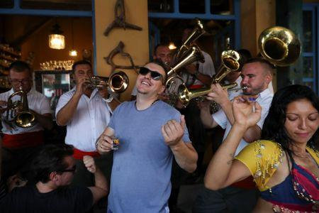 Revellers sing and dance as a band plays during the 57h Brass Band Festival, in the village of Guca