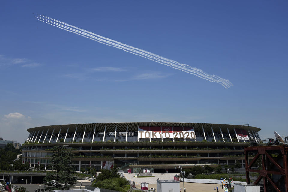 Blue Impulse of the Japan Air Self-Defense Force flies over the main National Stadium, Wednesday, July 21, 2021, in Tokyo. The National Stadium will host host the many of the events for the Tokyo 2020 Olympics that start July 23. (AP Photo/Eugene Hoshiko)