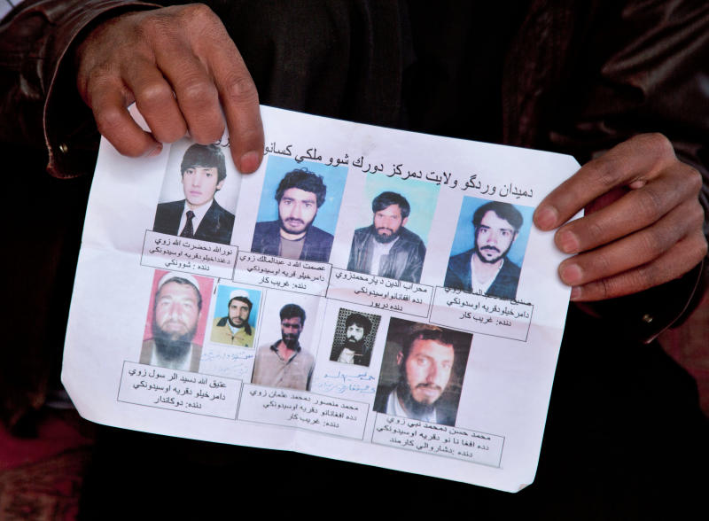 A missing-persons poster, with pictures of nine men who their relatives say were last seen being arrested by U.S. special operations forces, is held by a villager in Maidan Shahr, Afghanistan on Sunday, March 10, 2013. The posters were up for several months, but taken down after the bodies were found buried in a field near a U.S. base in Narkh district, about 15 kilometers (about 10 miles) from Maidan Shahr, capital of the Wardak province. An Afghan who once translated for the U.S. Special Forces was arrested on allegations of widespread torture and murder in connection with the disappearance and deaths of at least nine Afghans, the Afghan intelligence confirmed Monday, July 8, 2013. (AP Photo/Anja Niedringhaus)