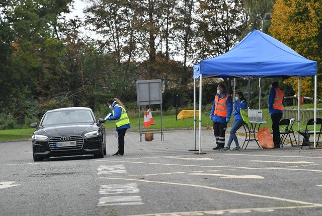 A tester is watched by her colleagues as she talks to the occupants of a car at a mobile coronavirus testing centre which has been set up at Stratford Park Leisure Centre in Stroud, Gloucestershire (Ben Birchall/PA