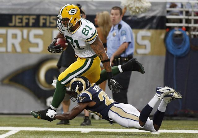Green Bay Packers tight end Andrew Quarless runs with the ball after catching a pass for a 35-yard gain as St. Louis Rams cornerback Lamarcus Joyner defends during the first quarter of an NFL preseason football game Saturday, Aug. 16, 2014, in St. Louis. (AP Photo/Scott Kane)