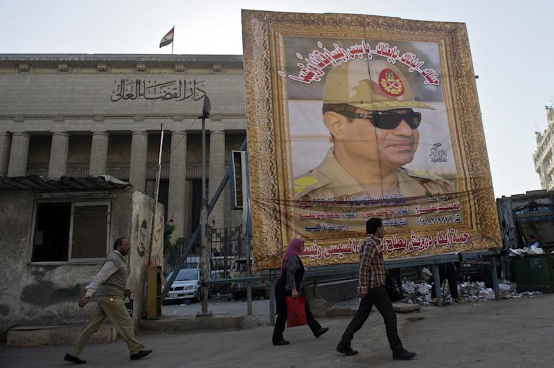 Egyptian walk past a huge poster of Egypt's former Defence Minister and armed forces chief General Abdul Fatah Al-Sisi outside the High Court in downtown Cairo, on March 27, 2014