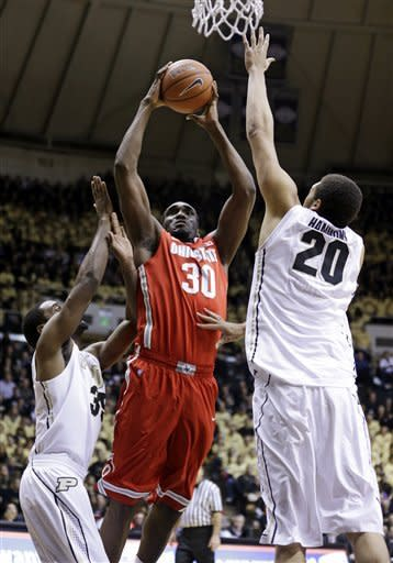 Ohio State forward Evan Ravenel (30) shoots between Purdue's Rapheal Davis, left, and A.J. Hammons (20) in the first half of an NCAA college basketball game in West Lafayette, Ind., Tuesday, Jan. 8, 2013. (AP Photo/Michael Conroy)