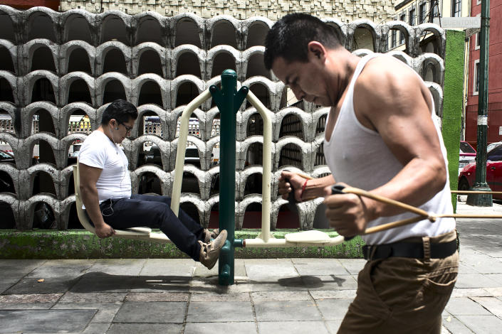 """<p>Two men doing exercise in a park in the center of Mexico City. The """"Gimnasios Urbanos"""" were built in 2016, with the goal of stimulating sports and physical exercise in the overweight population of Mexico City. (Photograph by Silvia Landi) </p>"""
