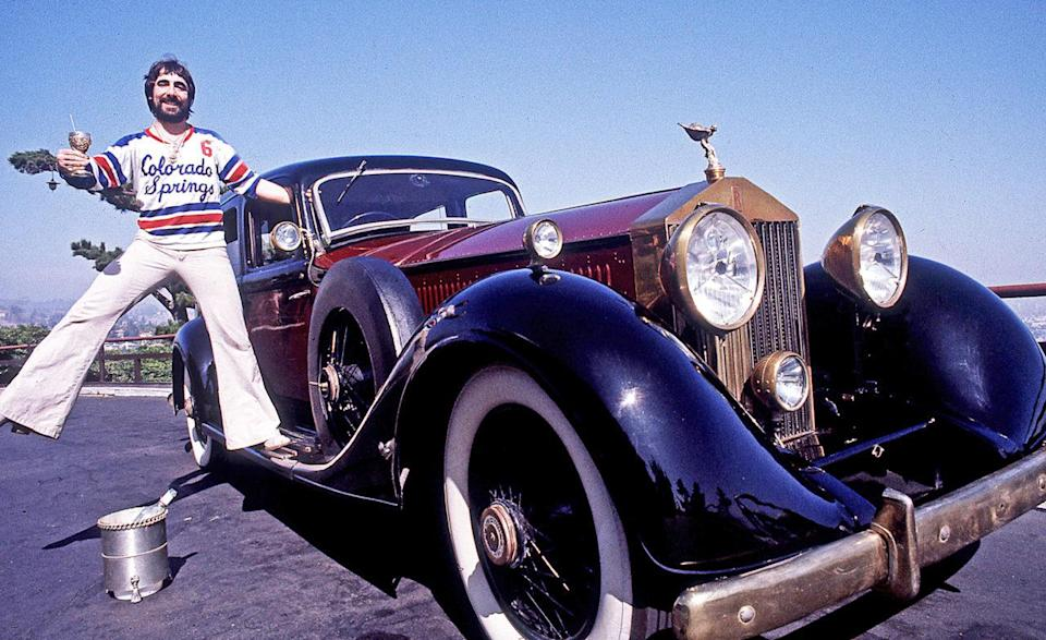 Keith Moon, The Who's Celebrated Drummer Standing On The Running Board Of His Classic Rolls-Royce Car On Mulholland Drive In The Hollywood Hills In Los Angeles, California, June 1976.