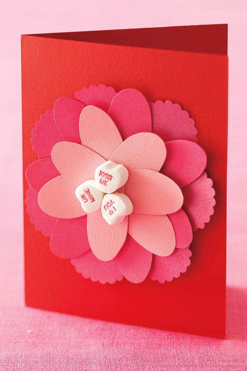"""<p>Lean on hearts of all kinds — paper<em> and</em> sugar — for a pretty card made by yours truly.</p><p><em><a href=""""https://www.womansday.com/home/crafts-projects/how-to/a5422/valentines-day-craft-how-to-cut-paper-flower-card-114599/"""" rel=""""nofollow noopener"""" target=""""_blank"""" data-ylk=""""slk:Get the tutorial at Woman's Day »"""" class=""""link rapid-noclick-resp"""">Get the tutorial at Woman's Day »</a> </em></p>"""