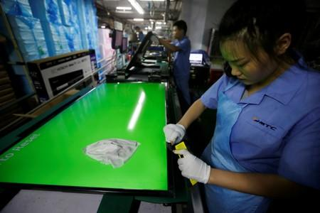 Employees work on the production line of a television factory under Zhaochi Group in Shenzhen