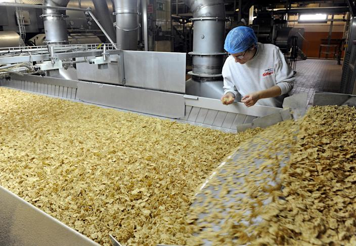 An employee of the Kellogg Deutschland GmbH examines the breakfast cereal 'Cornflakes' in the production in the Kellogg's plant in Bremen, Germany, 16 October 2013. For fifty years now, the different cornflakes products of the US cereal producer are produced in Bremen. The more than 100 year old company celebrated the 50 year anniversary of the Bremen plant. Photo: Ingo Wagner/dpa   usage worldwide (Photo by Ingo Wagner/picture alliance via Getty Images)