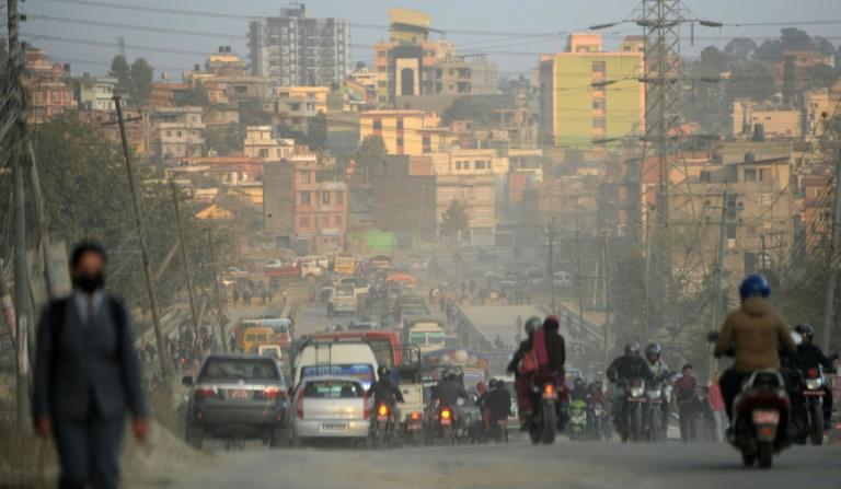 Vehicles and motorbike riders travel on a dusty road in Kathmandu