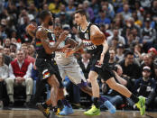Denver Nuggets forward Juan Hernangomez, front, right, passes the ball to guard Will Barton, front left, as Charlotte Hornets forward Marvin Williams defends during the first half of an NBA basketball game Wednesday, Jan. 15, 2020, in Denver. (AP Photo/David Zalubowski)