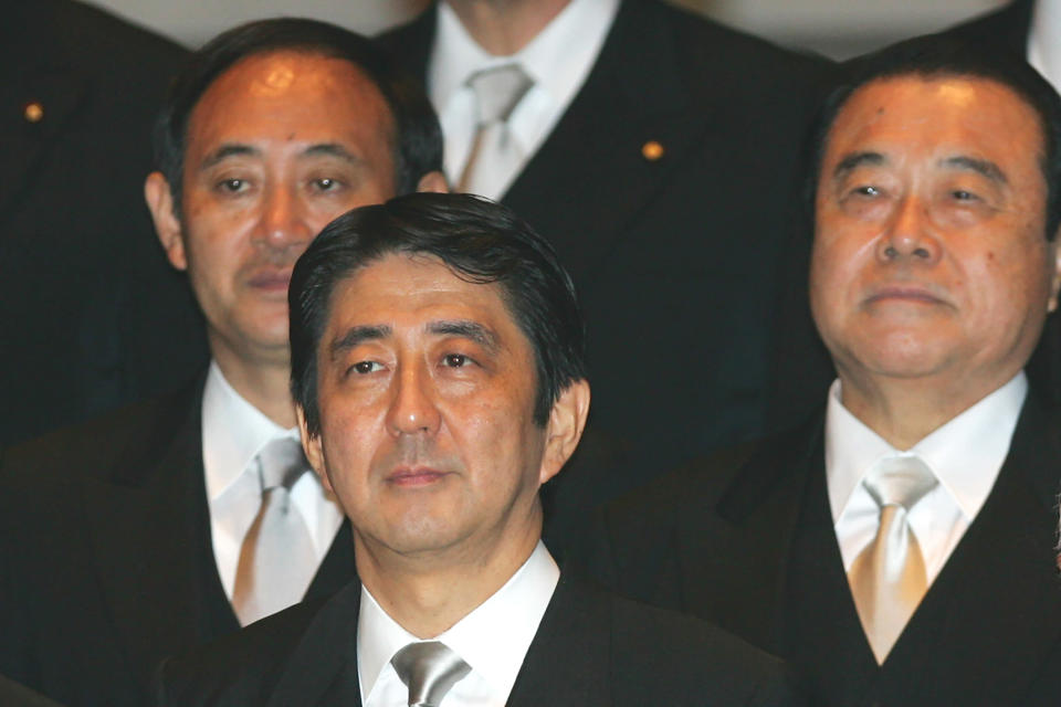 FILE - In this Sept. 26, 2006, file photo, then newly-appointed Japanese Prime Minister Shinzo Abe, front row, poses with his Cabinet members after an attestation ceremony for his Cabinet at the Imperial Palace in Tokyo. Then Internal Affairs and Communications Minister Yoshihide Suga, rear left, and then Land, Infrastructure and Transport Minister Tetsuzo Fuyushiba stand behind Abe. Japan's Parliament elected Suga as prime minister Wednesday, Sept. 16, 2020, replacing long-serving leader Abe with his right-hand man. (AP Photo/Itsuo Inouye, File)