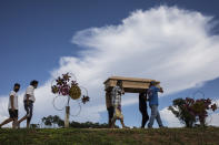 Relatives carry the coffin that contain the remains of Daniel Sevillano, who died from COVID-19, to a burial site burial in Iquitos, Peru, Tuesday, March 23, 2021. (AP Photo/Rodrigo Abd)