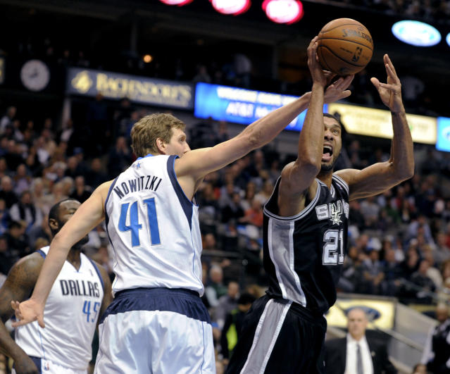 Dallas Mavericks forward Dirk Nowitzki (41) defends a shot by San Antonio Spurs forward Tim Duncan (21) during the first half of an NBA basketball game, Thursday, Dec. 26, 2013, in Dallas. (AP Photo/Matt Strasen)