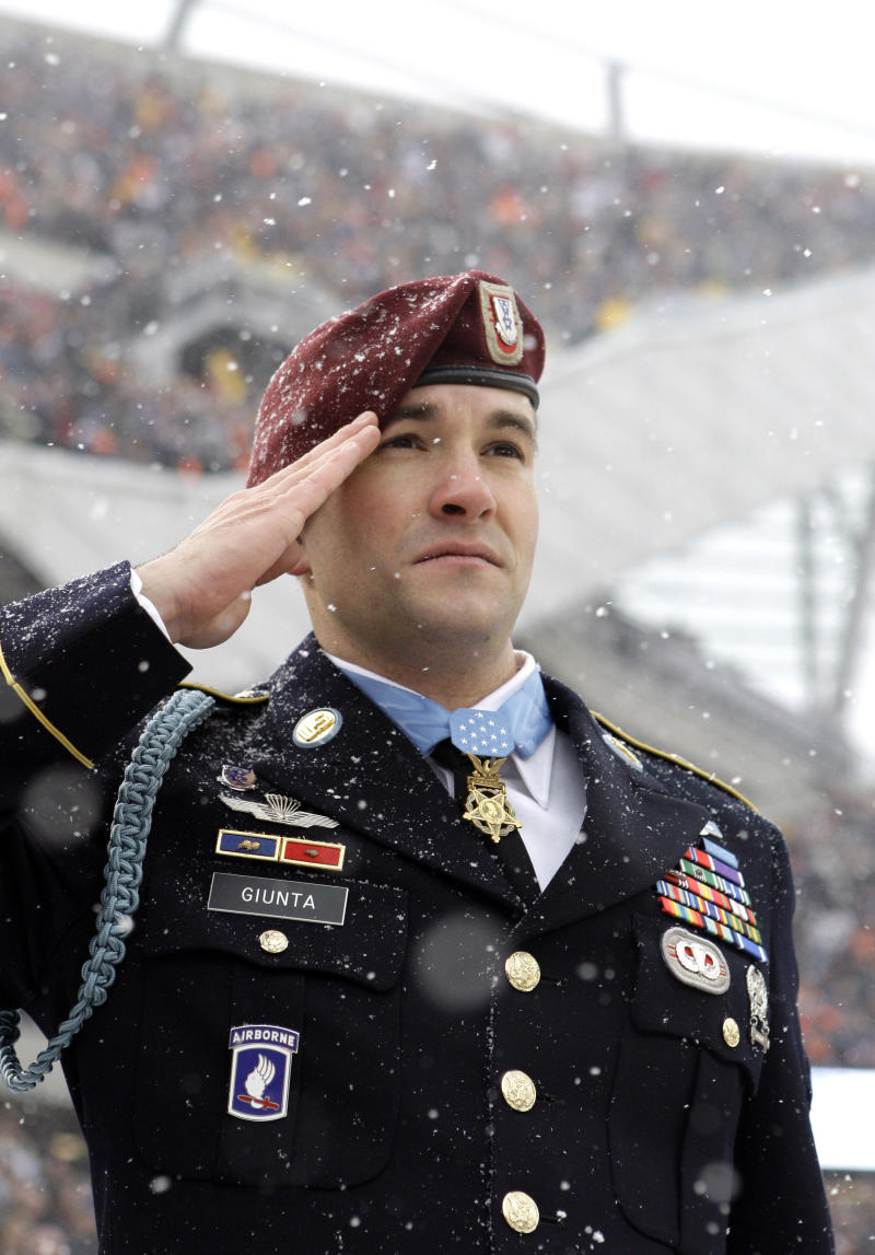In this Dec. 12, 2010 photo, Staff Sgt. Salvatore Giunta, first living Medal of Honor recipient for service in Iraq or Afghanistan and the first living recipient of the Medal of Honor since the Vietnam War, salute during the National Anthem before an NFL football game between New England Patriots and Chicago Bears in Chicago. The award has thrust Giunta into the spotlight. But through it all, the 25-year-old-combat veteran has remained a modest man in a 'look at me' world. He insists he's an average soldier, but the gold five-point star around his neck says otherwise. (AP Photo/Nam Y. Huh, File)