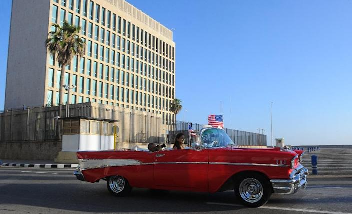 A vintage car with US flags drives by the US embassy in Havana, on July 20, 2015 (AFP Photo/Yamil Lage)
