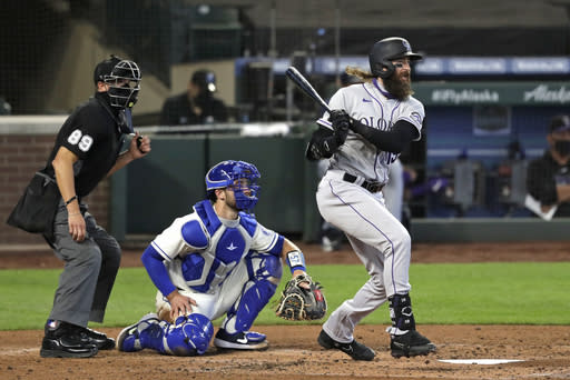 Colorado Rockies' Charlie Blackmon, right, watches the path of his single as Seattle Mariners catcher Joe Hudson, center, and umpire Cory Blaser look on in the fourth inning of a baseball game Sunday, Aug. 9, 2020, in Seattle. (AP Photo/Elaine Thompson)