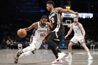 Brooklyn Nets guard Kyrie Irving (11) drives around Atlanta Hawks forward De'Andre Hunter (12) as Nets guard Joe Harris (12) watches, right, during the second half of an NBA basketball game, Sunday, Jan. 12, 2020, in New York. The Nets defeated the Hawks 108-86. (AP Photo/Kathy Willens)