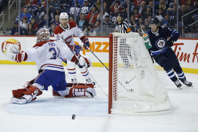 A shot by Winnipeg Jets' Patrik Laine (29) shot rings off the post behind Montreal Canadiens goaltender Carey Price (31) during the second period of an NHL hockey game Saturday, March 30, 2019 in Winnipeg, Manitoba. (John Woods/The Canadian Press via AP)