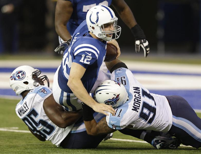 Indianapolis Colts' Andrew Luck (12) is sacked by Tennessee Titans' Kamerion Wimbley (95) and Derrick Morgan (91) during the first half of an NFL football game on Sunday, Dec. 1, 2013, in Indianapolis. (AP Photo/Michael Conroy)