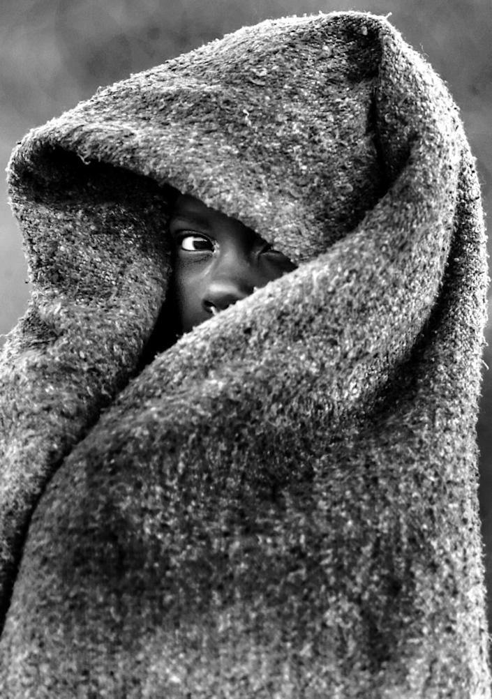 A child wrapped in a blanket; only part of their face is visible