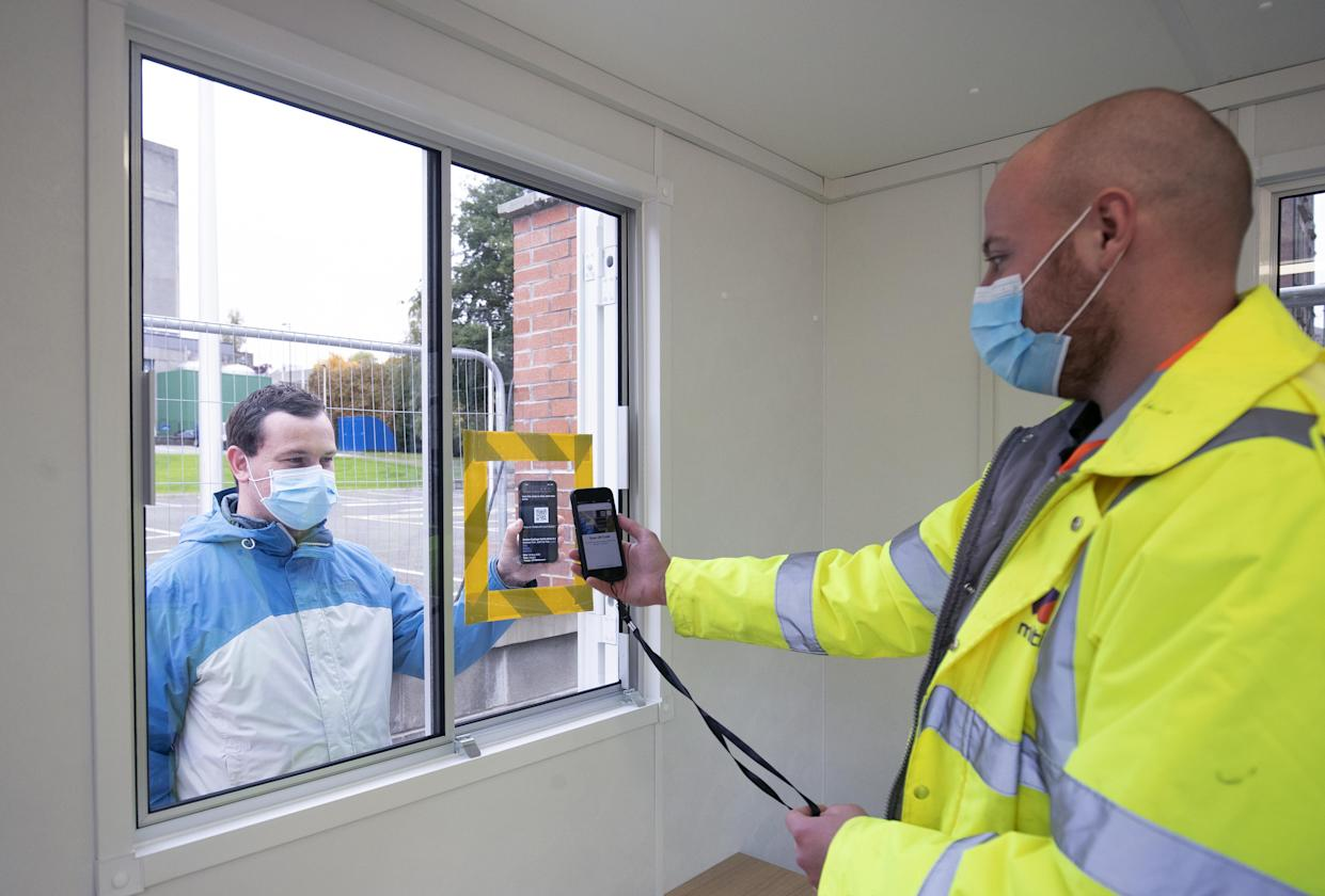 Andrew Ilesley gets his QR code scanned using a smart phone to demonstrate how to use the new walk-through Covid testing centre in Dundee. The test centre uses a system of connected trailers cleaned using dry ice, the first site in Scotland to have this capability. (Photo by Jane Barlow/PA Images via Getty Images)