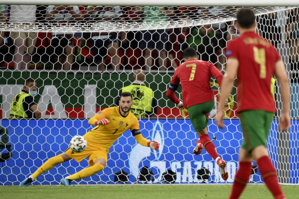 Portugal's Cristiano Ronaldo scores the opening goal from the penalty spot during the Euro 2020 soccer championship group F match between Portugal and France at the Puskas Arena in Budapest, Wednesday, June 23, 2021. (Franck Fife, Pool photo via AP)