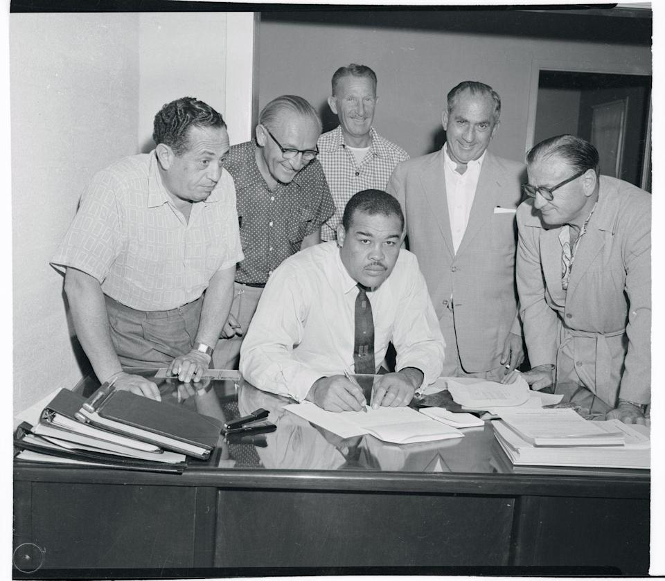 <p>Former heavyweight champion Joe Louis signs a contract purchasing part interest in Las Vegas's $3,000,000 Moulin Rouge Hotel in 1954.</p>