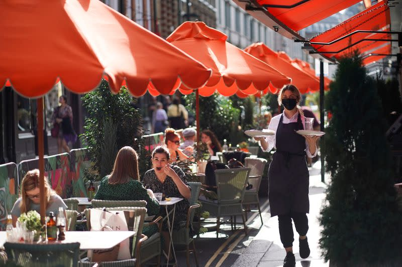 FILE PHOTO: People sit at tables outside restaurants in Soho, amid the coronavirus disease (COVID-19) outbreak, in London