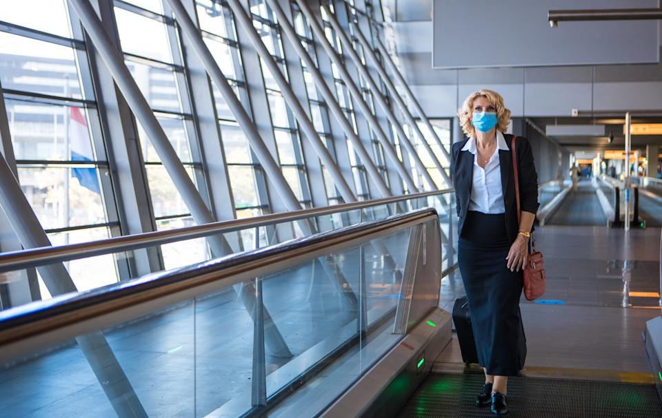 A beautiful blonde female air traveller respecting corona virus practices during the covid-19 virus pandemic at an airport terminal