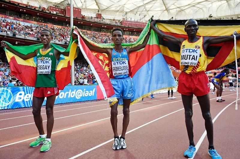 Gold medallist Ghirmay Ghebreslassie (C) celebrates with silver medallist Yemane Tsegay (L) and bronze medallist Munyo Solomon Mutai after winning the men's marathon, during the IAAF World Championships in Beijing, on August 22, 2015 (AFP Photo/Franck Fife)