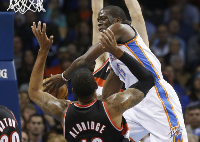 Oklahoma City Thunder guard Reggie Jackson, right, drives past Portland Trail Blazers forward LaMarcus Aldridge (12) in the first quarter of an NBA basketball game in Oklahoma City, Tuesday, Jan. 21, 2014. (AP Photo/Sue Ogrocki)